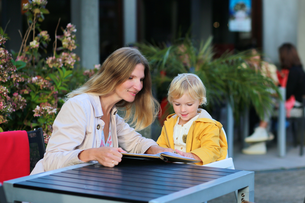 Mom reading to child at a table to teach print awareness
