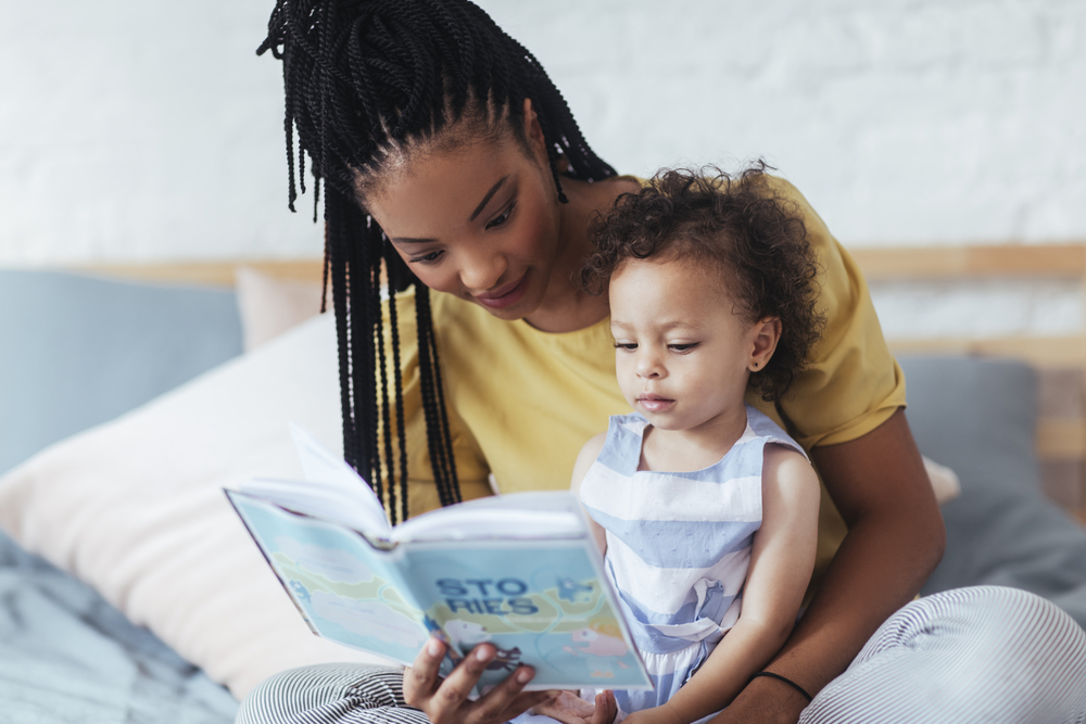 Mom reading to young daughter teaching her print awareness