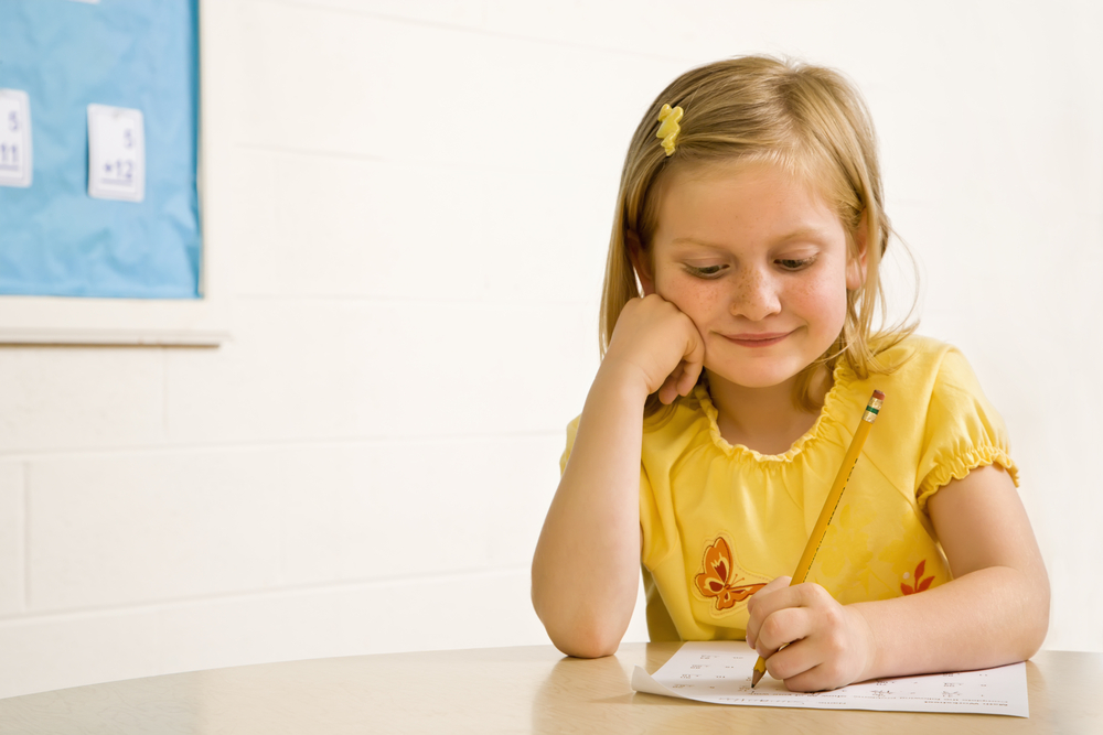 Young girl writing spelling words on paper
