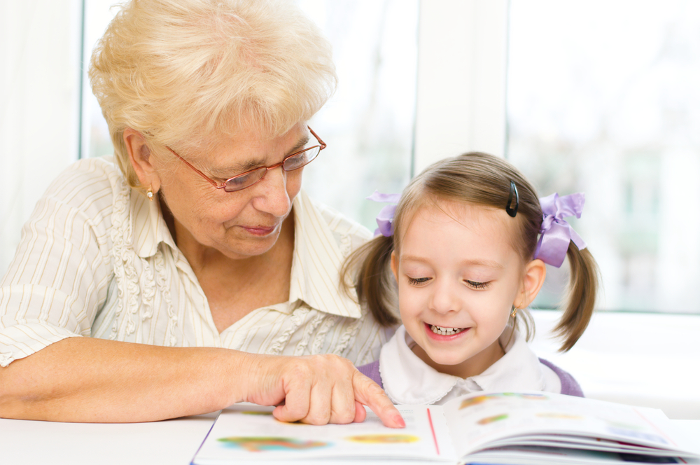 A grandmother teaching her grand daughter syllables