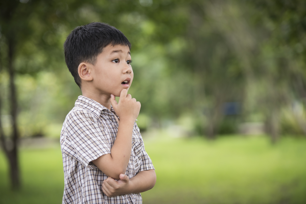 Portrait of cute little asian boy hand under chin And Thinking While Standing over the blurred background.