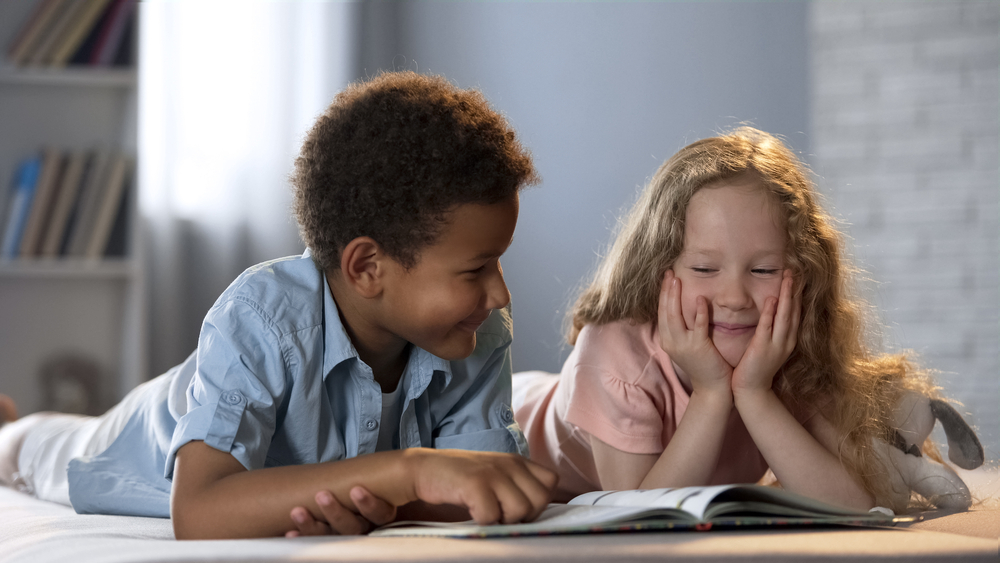 Two kids learning syllables while reading