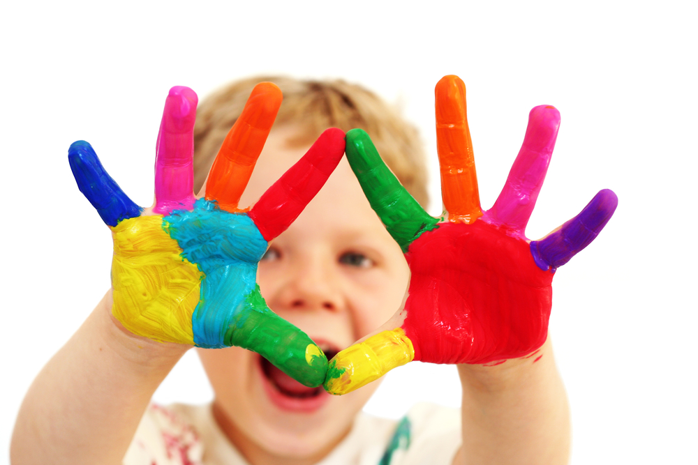 Four year old boy with hands painted in colorful paints ready for hand prints