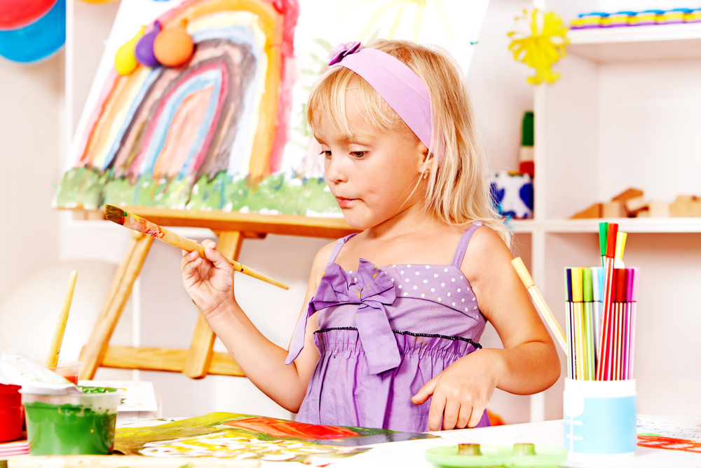 Little girl painting at easel in school.