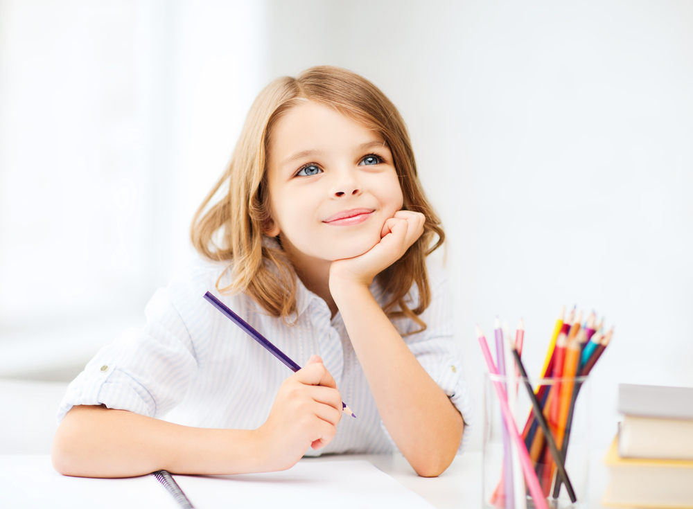 little student girl drawing with pencils at school