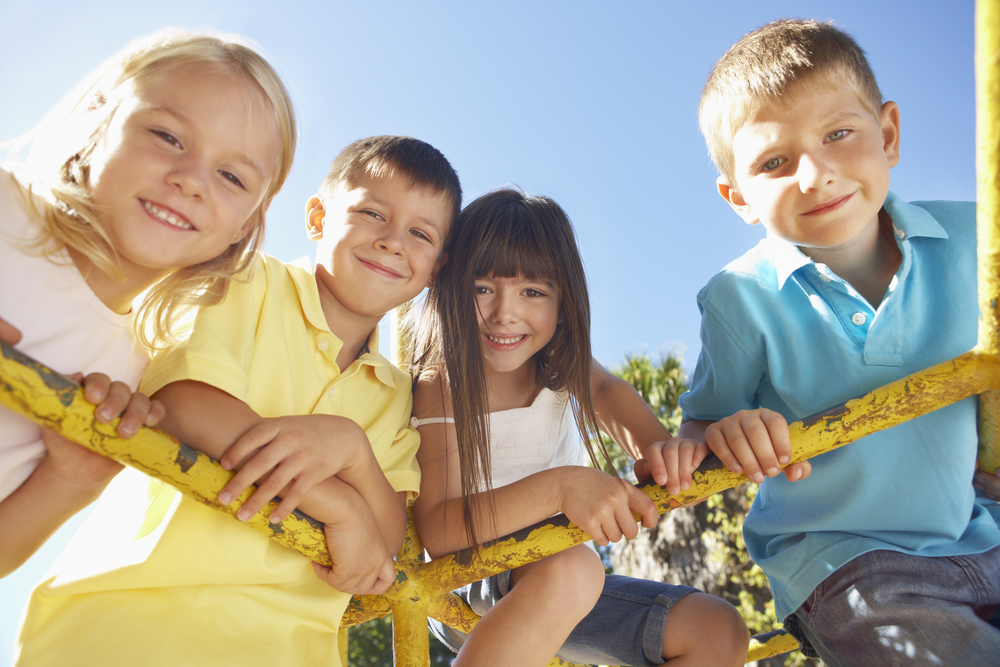 4 kids hanging on a jungle gym