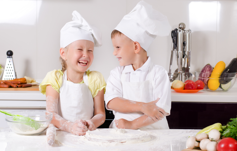 Two kids baking in bakers hats and aprons