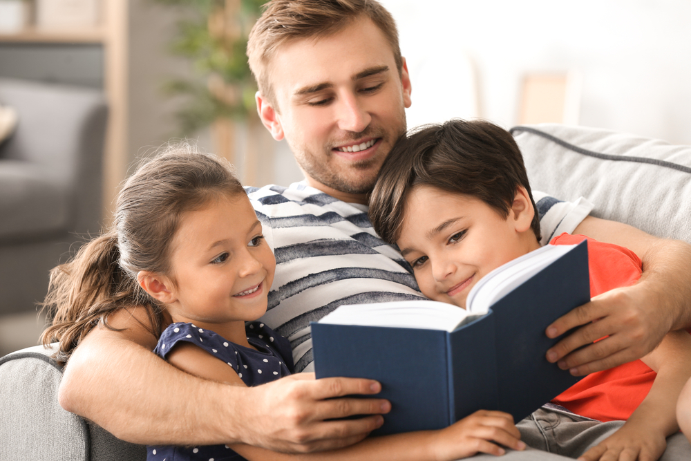 Dad reading to his children and explaining adjectives for kids
