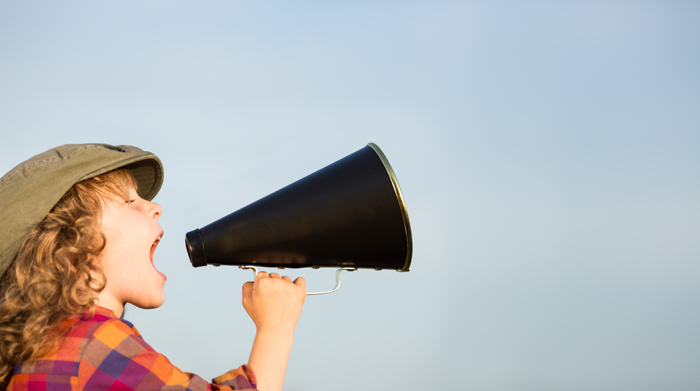 Kid shouting through vintage megaphone.