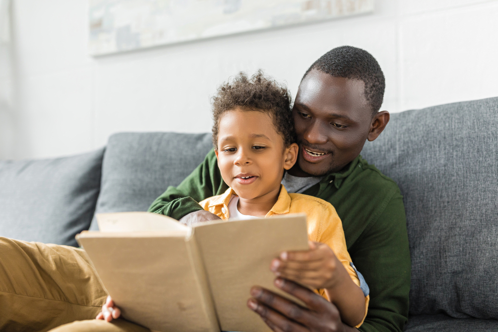 Parent teaching adjectives for kids by reading to his son
