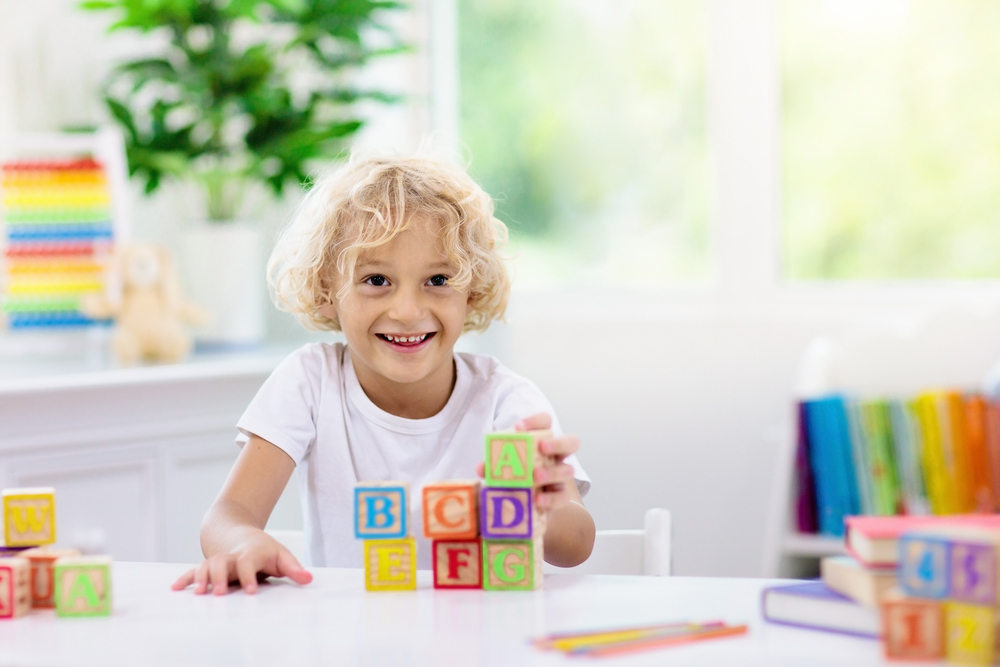 Kid with colorful wooden abc blocks.