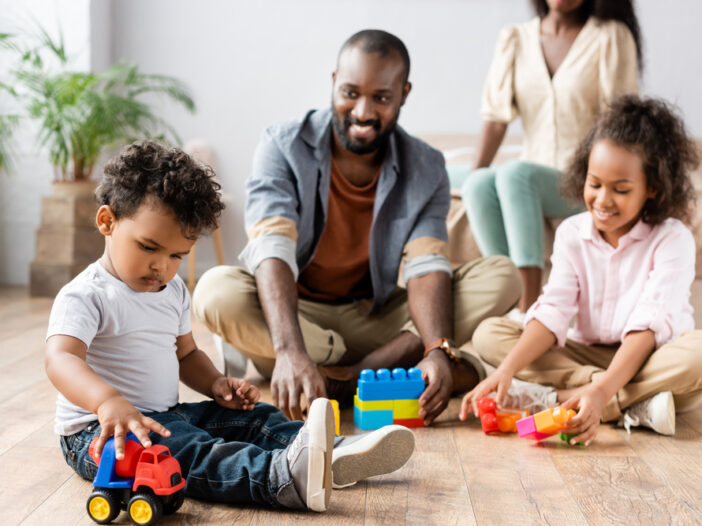 Dad playing blocks with kids to teach them cooperative play
