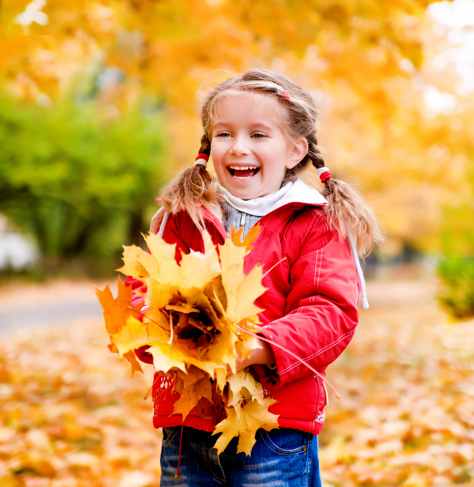 Kid playing leaves in the fall