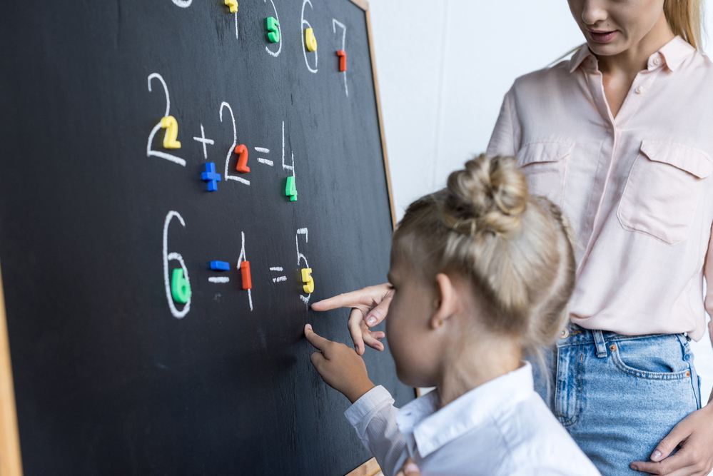 Child and teacher doing math on a chalkboard