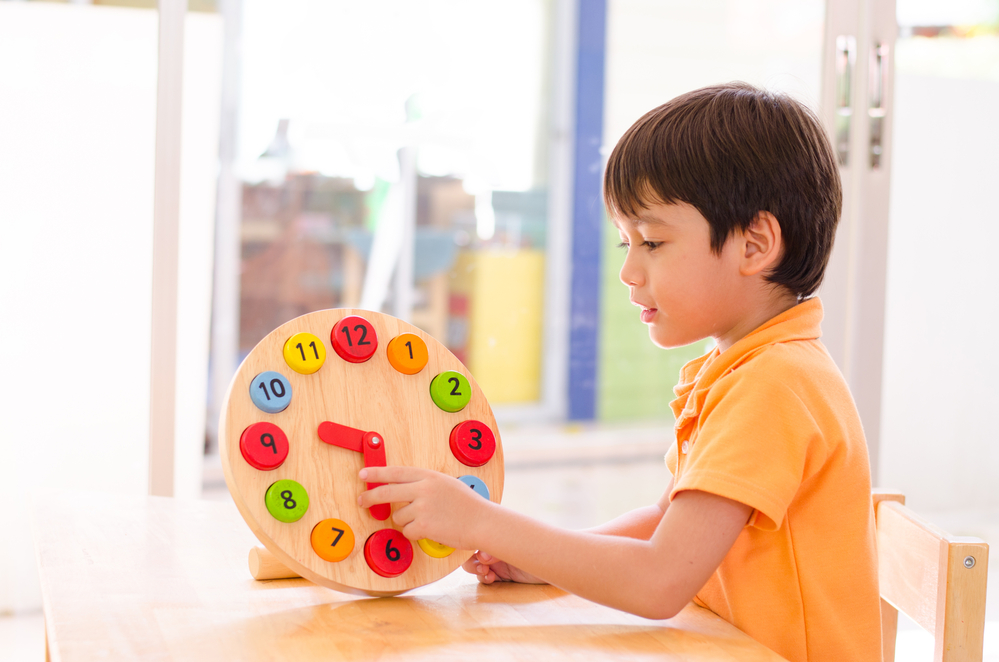 kid using a play clock to learn and tell time