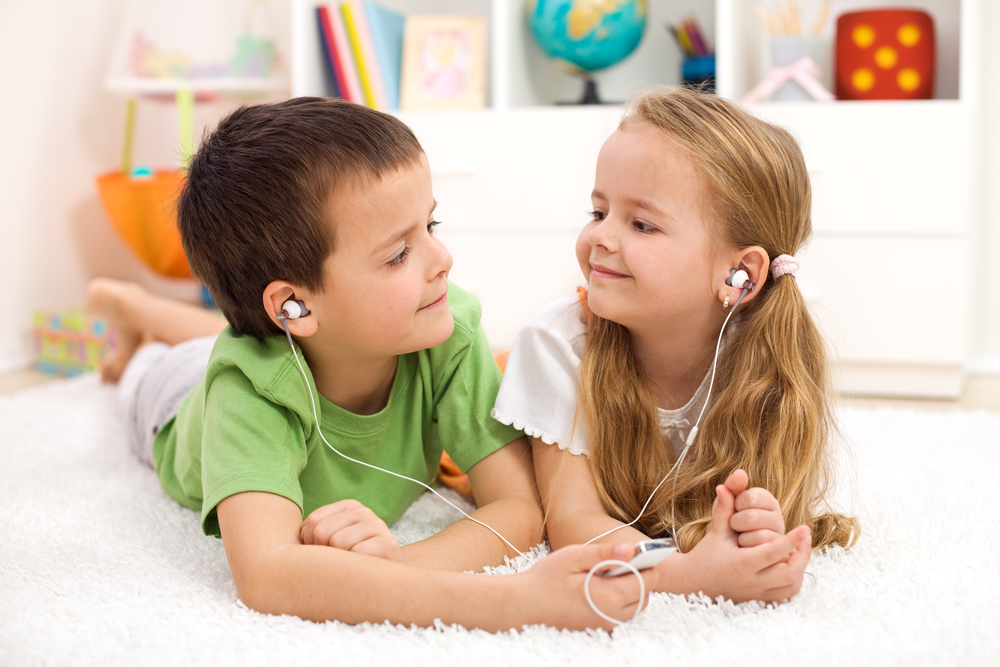 two kids sharing headphones to listen to music