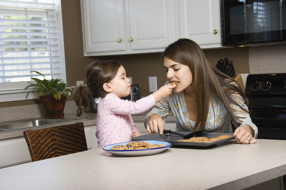kids sharing a cookie with her mom