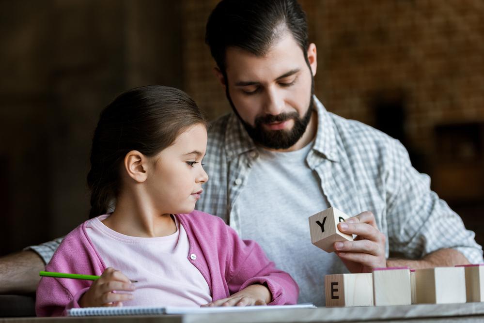 Dad teaching daughter the alphabet using letter blocks