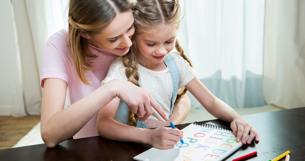 Child learning the alphabet with the help of her mom