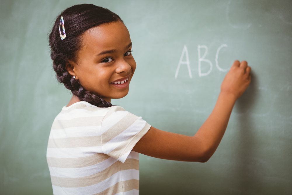 Child learning the alphabet by writing letters on a chalkboard