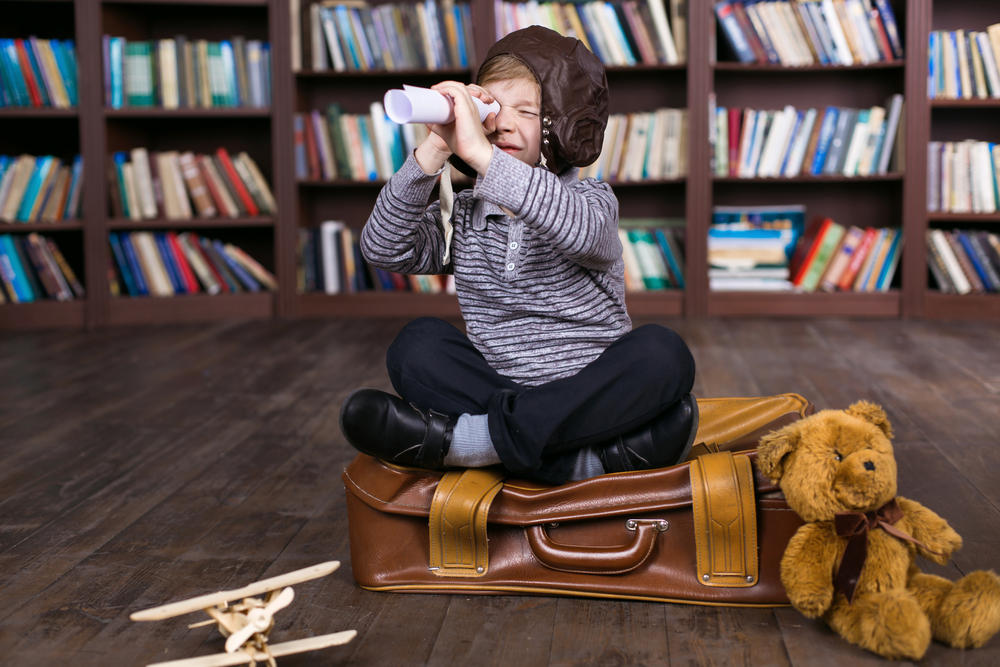 Little boy having fun at room with bookshelf and sitting on suitcase.