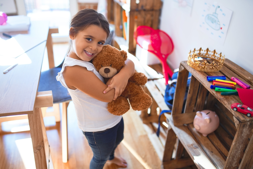 Adorable toddler smiling happy hugging teddy bear around lots of toys at kindergarten