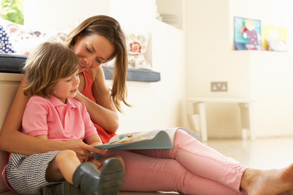 Mother Sitting With Son Reading showing him the difference between uppercase and lowercase letters