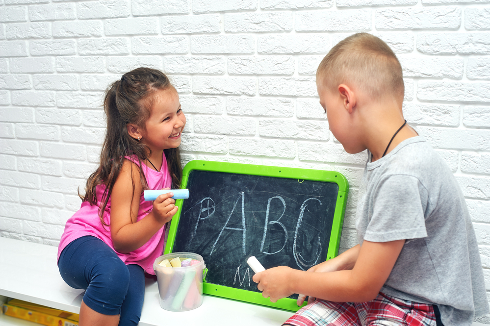 Two kids writing uppercase letters on a chalk board