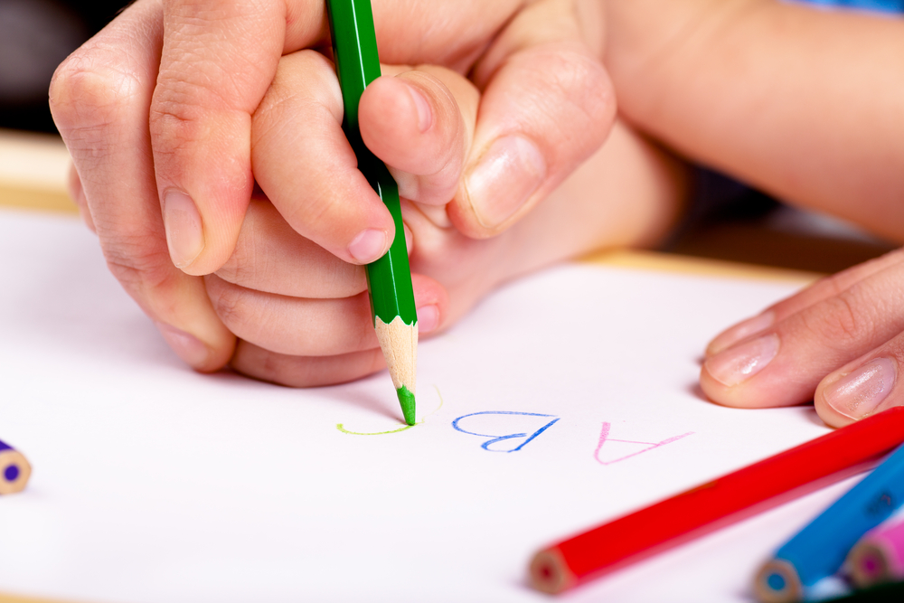 Child hand with pencil and woman hand helping to write Uppercase Letters