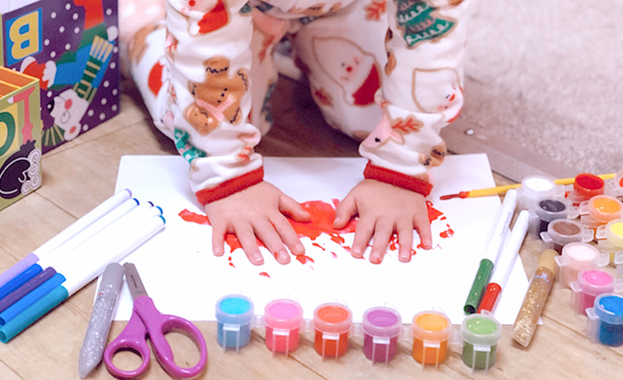 A child is making handprints on some paper